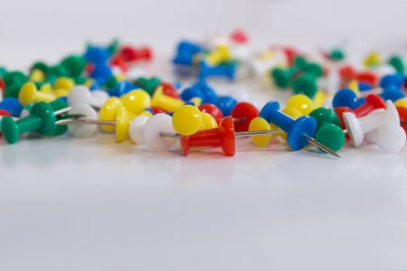 Many colorful push pins on the background, close-up photo