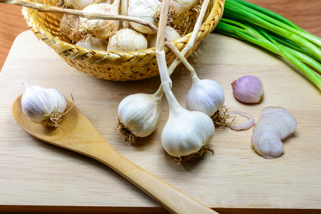 garlic clove: sliced garlic, garlic clove, garlic bulb in wicker basket place on chopping block