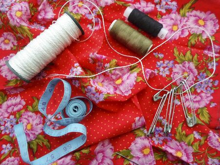 yarn needles pins on red fabric