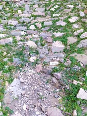 real stone wall without cement. old road with stones grass. stone road background image old road 写真素材
