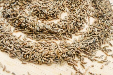 heap of caraway seeds on a wooden table