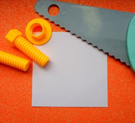 toy tools, saw, bolts and nuts on an orange background. white sheet of paper place for text