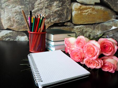 September 1 concept. Books, flowers, pencils on a black table. September 1 is the word in Russian. side view