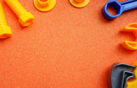 blue and orange toy tools on a dark orange background. wrenches and other toy tools