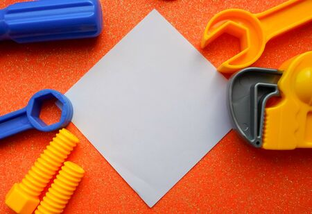 toy tools, wrench and others on an orange background. white sheet of paper place for text Stok Fotoğraf