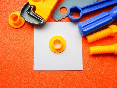 toy tools, wrench and others on an orange background. white sheet of paper place for text 写真素材 - 130046602