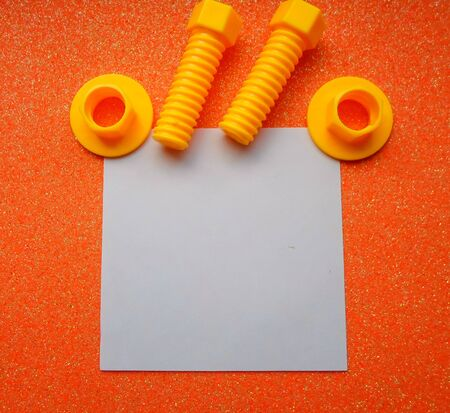 toy tools, bolts and nuts on an orange background. white sheet of paper place for text 写真素材 - 130046601