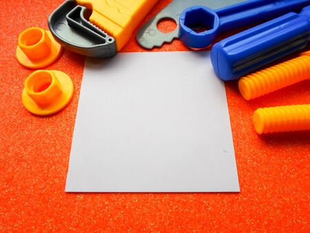 toy tools, wrench and others on an orange background. white sheet of paper place for text 写真素材 - 130046308