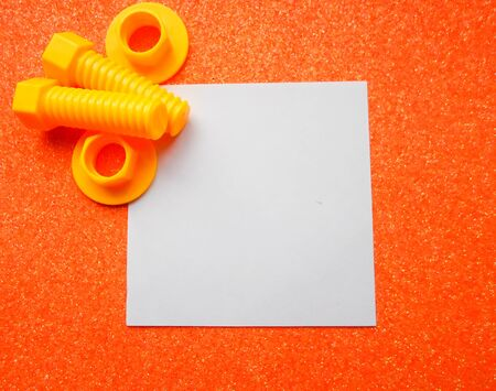 toy tools, bolts and nuts on an orange background. white sheet of paper place for text 写真素材 - 130046314