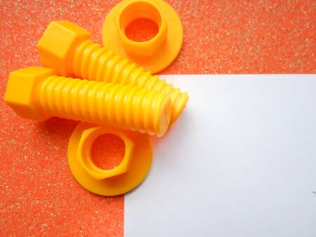 toy tools, bolts and nuts on an orange background. white sheet of paper place for text 写真素材 - 130045377