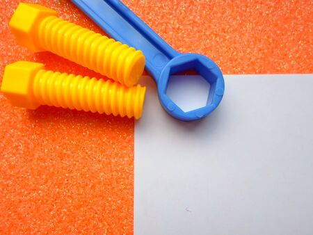toy tools, wrench and others on an orange background. white sheet of paper place for text 写真素材 - 130045379