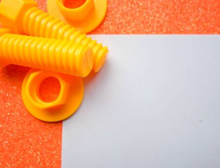 toy tools, bolts and nuts on an orange background. white sheet of paper place for text