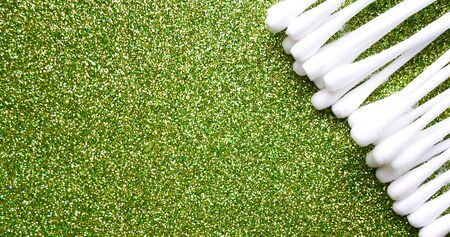 Cotton buds of white color on a green background. daily cleaning with cotton buds, ear hygiene Stock Photo