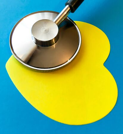Top view a stethoscope and a yellow heart on a dark blue background, medical and healthy concept.