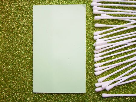 Cotton sticks of white on a green background and a sheet of paper for writing. daily cleaning with cotton buds, ear hygiene Stock Photo - 130512096