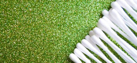 Cotton buds of white color on a green background. daily cleaning with cotton buds, ear hygiene Stok Fotoğraf