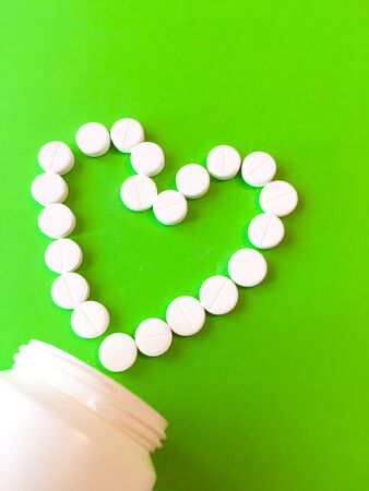 The pills are laid out in the shape of a heart and a white bottle. On a green background. View from above. Space for text.