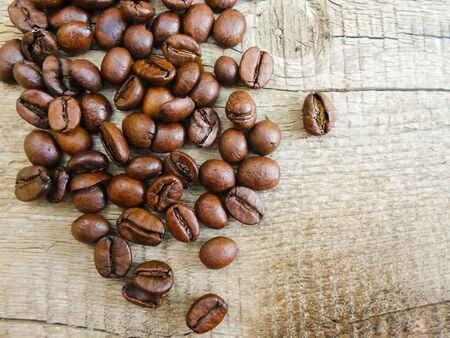 Large grains of coffee on a wooden table. place for text. background image 写真素材