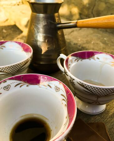 Turkish coffee on a wooden table and three empty cups of coffee