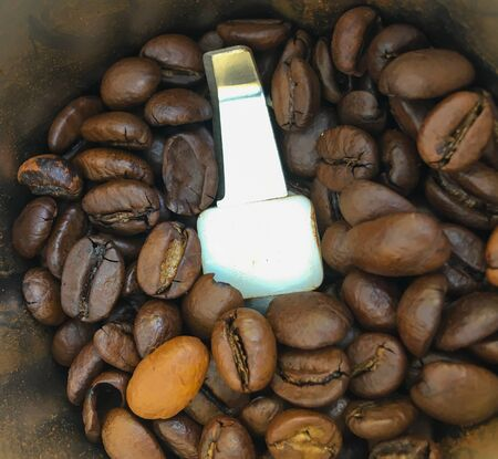 coffee grinder with roasted coffee beans.Macro photo of freshly ground coffee in an electric coffee grinder. 写真素材