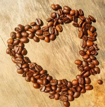 Heart shape made from coffee beans on wooden background, Coffee beans in the shape of a heart, roasted coffee beans in the shape of a heart. heart background