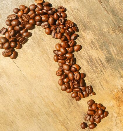 Coffee beans are arranged in the form of a question mark on a wooden background.