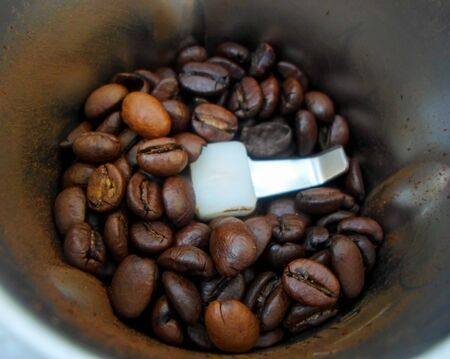 coffee grinder with roasted coffee beans. Macro photo of freshly ground coffee in an electric coffee grinder.