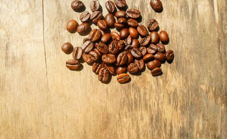 large grains of coffee on a wooden table. place for text