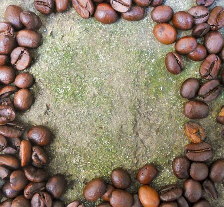 large grains of coffee on a concrete surface. coffee beans with place for text