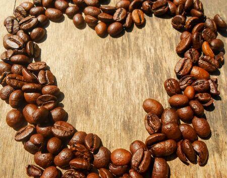 木製の背景にコーヒー豆から作られたハートの形、ハートの形をしたコーヒー豆、ハートの形をした焙煎コーヒー豆。心臓の背景