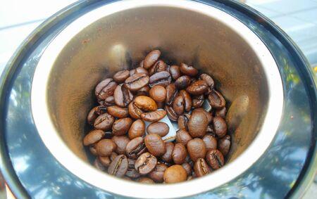 焙煎コーヒー豆のコーヒーグラインダー。電気コーヒーグラインダーで挽きたてのコーヒーのマクロ写真。