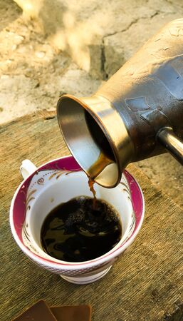 Turkish coffee on a wooden table and one empty cup of coffee
