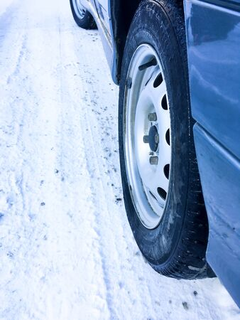 Close-up of car tires in winter on a snow covered road. Car tires on a winter road covered in snow. Car on a snowy path in the morning with snowfall Stockfoto