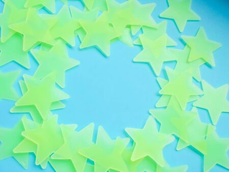 blue background with yellow-green stars laid out in the shape of a circle, free space for your text. Bright star-shaped paper on a blue fabric background.