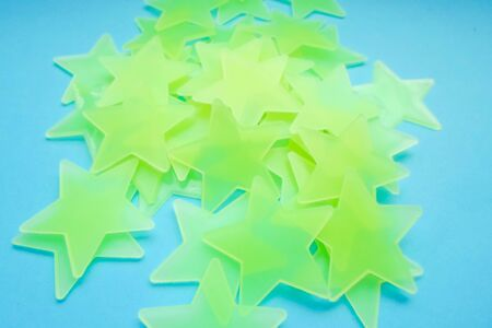 blue background with yellow-green stars, free space for your text. Star shaped bright paper on a blue fabric background Zdjęcie Seryjne