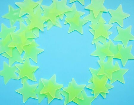 blue background with yellow-green stars laid out in the shape of a circle, free space for your text. Bright star-shaped paper on a blue fabric background. Foto de archivo - 137897198