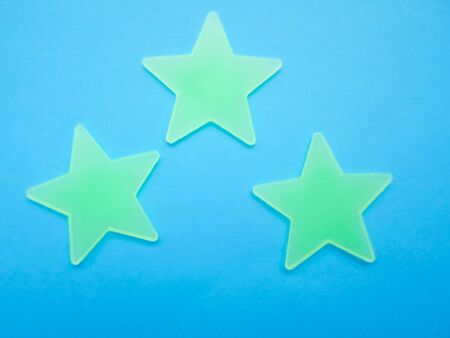 green stars glowing in the dark on a blue background. stars with place for text