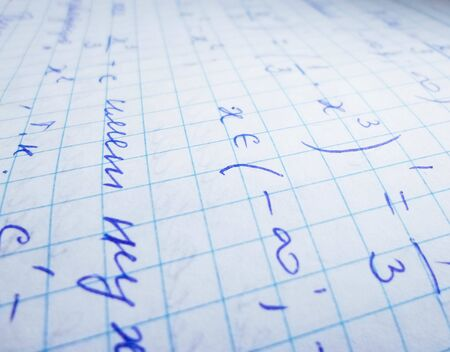 mathematical formulas are written in a notebook. solution school examples in algebra and geometry