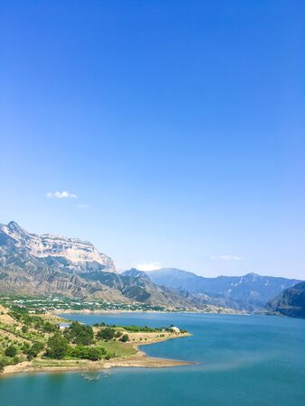 clear sky over a lake in the Caucasus in a mountain village visible roofs of houses. Lake and mountains of the Caucasus against a clear blue sky. Dagestan mountains. Hydroelectric power station in the
