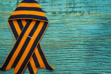 St. George ribbon on a wooden background. Symbol of courage and victory, May 9 and February 23.