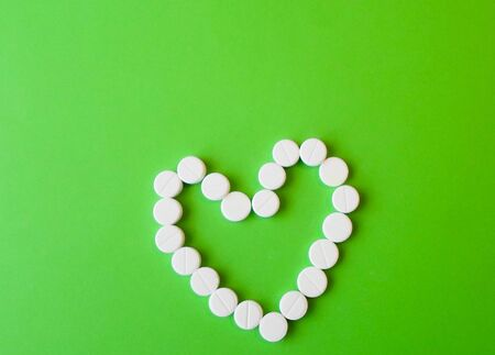 white pills on a green background in the shape of a heart. snow-white round antibiotics against viruses. protection against harmful bacteria