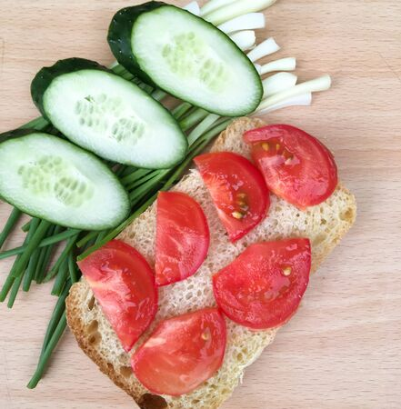 sandwich with bread with tomatoes and cucumbers and onions on a wooden table. healthy breakfast for every day