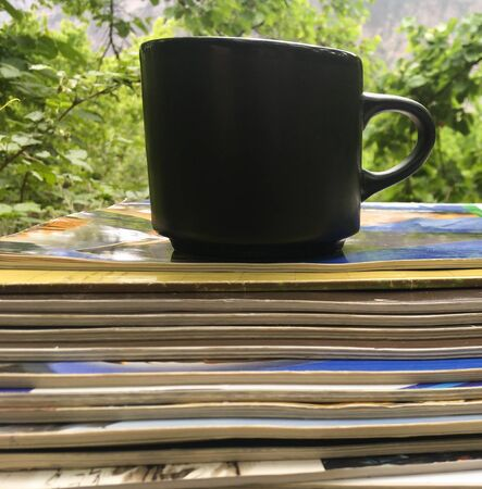 a stack of fresh morning Newspapers and a Cup of coffee against a background of greenery. A Cup of hot coffee and Newspapers in the garden in the morning