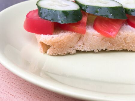 sandwich with bread with tomatoes and cucumbers on a plate on a wooden table. healthy breakfast for every day