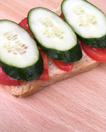sandwich with bread with tomatoes and cucumbers on a wooden table. healthy breakfast for every day