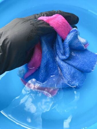in a blue basin wash a multi-colored napkin with a female hand in black gloves