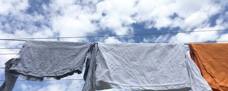 clothes hanging after washing. shirts to dry on a cloudy sky background.