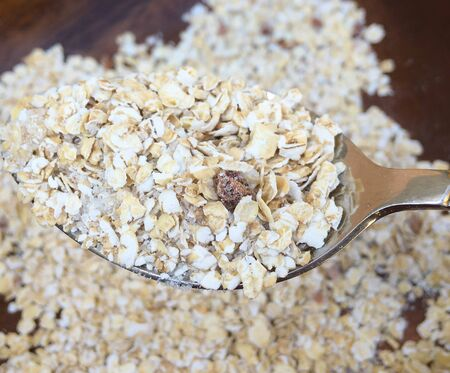 delicious oatmeal sprinkled on a table from a plate and a full spoon of oatmeal Foto de archivo