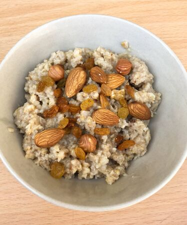 tasty oatmeal with raisins and nuts in a plate on a wooden table. healthy breakfast for every day