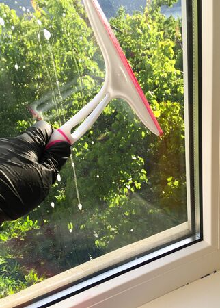 Window cleaning with detergent, spring cleaning concept.Hand in a black glove with a special tool washes a soap window on a background of trees
